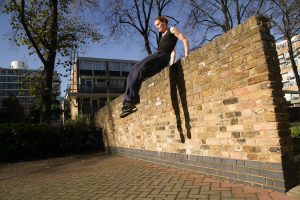 female parkour athlete vaults wall